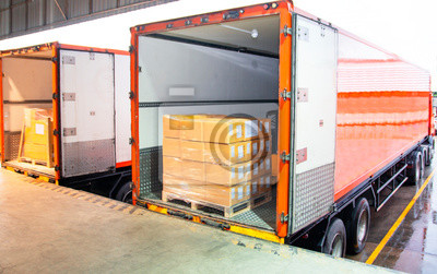Obraz freight transportation, cargo courier shipment. stacked cardboard boxes wrapping plastic load into a truck container at dock warehouse.
