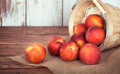 Obraz Fresh peach fruits in a basket, rustic wooden background