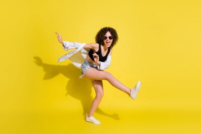 Obraz Full length body size photo of crazy girl wearing casual clothes laughing dancing kicking isolated on vivid yellow color background