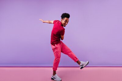 Obraz Full-length shot of trendy african male model in pink clothes. Excited black man in stylish sneakers dancing on purple background.