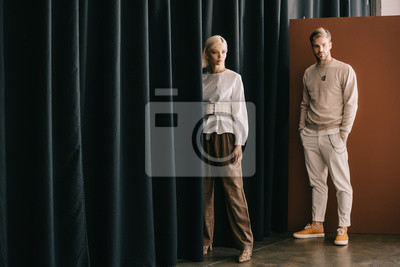 Obraz full length view of elegant blonde woman and bearded man standing near curtain