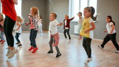 Obraz Full of energy. Group of little boys and girls dancing while having choreography class in the dance studio. Female dance teacher and children