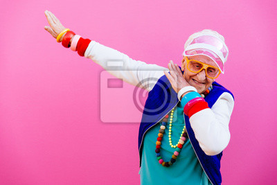 Obraz Funny grandmother portraits. 80s style outfit. Dab dance on colored backgrounds. Concept about seniority and old people