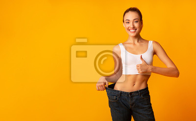 Obraz Girl In Oversize Jeans Gesturing Thumbs Up Smiling, Yellow Background