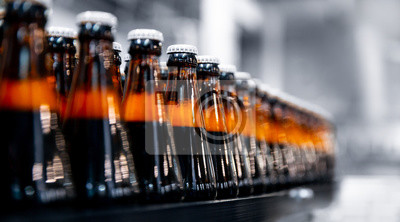 Obraz Glass bottles of beer on dark background with sun light. Concept brewery plant production line