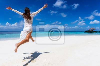 Obraz Glückliche Frau in weißem Sommerkleid läuft an einem tropischen Paradies Strand und genießt ihren Urlaub auf den Malediven