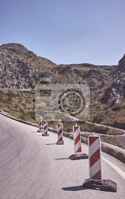 Górska kręta droga z przenośnymi ostrzegawczymi znakami drogowymi, zdjęcie w stonowanych kolorach.