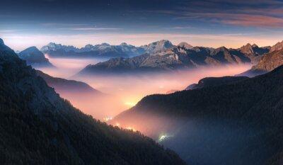 Obraz Góry w mgle przy piękną nocą w jesieni w dolomitach, Włochy. Krajobraz z alpejską górską doliną, niskie chmury, las, kolorowe niebo z gwiazdami, iluminacja miasta o zmierzchu. Antenowy. Passo Giau
