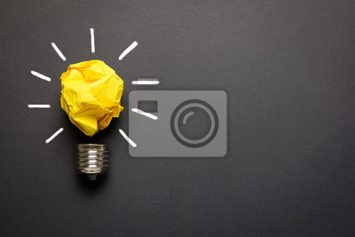 Obraz Great idea concept with crumpled yellow paper light bulb isolated on dark background
