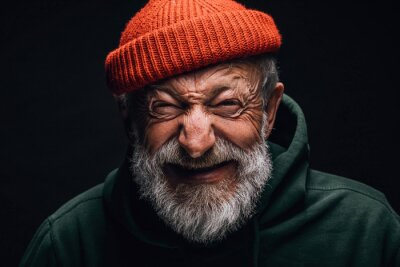 Obraz Grey- haired aged grandfather feeling overjoyed and excited while telling about his trip to mountains. Old man dressed in red knitted hat and green hoodie. Happy to be active in retirement