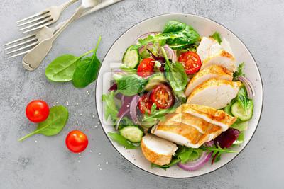 Obraz Grillowana pierś z kurczaka, filet i sałata ze świeżych warzyw, sałata, rukola, szpinak, ogórek i pomidor. Zdrowe menu na lunch. Dietetyczne jedzenie. Widok z góry