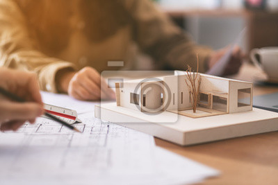 Obraz Group of an architect working and discussing about an architecture model together with shop drawing paper on table in office