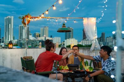 Obraz Group of Asian millennial people friends toasting alcoholic drink shot glasses while having outdoor dinner party with eat barbecue grill at rooftop for meeting reunion and holiday celebration together