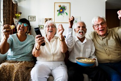 Obraz Group of cheerful senior friends sitting and watching TV together