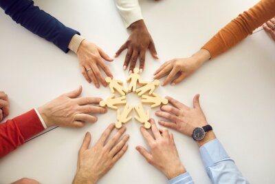 Obraz Group of diverse people arrange human figures in circle. Team of multiethnic business partners join little wooden figures on table. Teamwork, community, working together and cooperation metaphor
