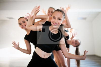 Obraz Group of fit happy children exercising dancing and ballet in studio together