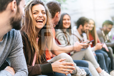 Obraz Group of trendy young people chatting together sitting on a bench outdoors. Students having fun together. Focus on a blonde girl smiling with open mouth