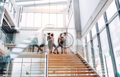 Obraz Group of young businesspeople standing on a staircase, talking.