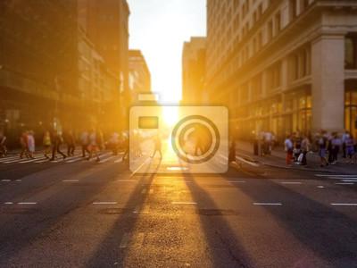 Grupa anonimowych ludzi chodzi po drugiej stronie ulicy na 5th Avenue w Manhattan Nowy Jork z ustawieniem światła słonecznego w tle