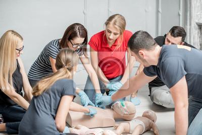 Obraz Grupa ludzi uczących się, jak wykonywać pomiary serca pierwszej pomocy z manekinami podczas treningu w pomieszczeniu