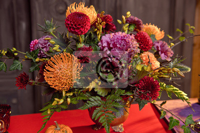Obraz Halloween pumpkin decor with candles and a bouquet of flowers in a bronze vase on a red tablecloth