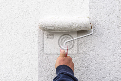 Obraz hand holds  paint roller and painting  a wall