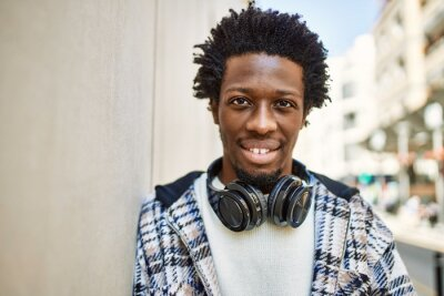 Obraz Handsome black man with afro hair wearing headphones smiling happy outdoors