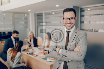 Obraz Handsome smiling businessman in formal wear and eyeglasses standing at boardroom with arms crossed. Love and respect do not automatically accompany a position of leadership. They must be earned