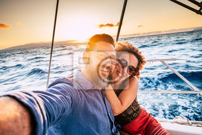 Obraz Happy and cheerful people enjoying the travel and trip on a sail boat with ocean and sunset sunlight in background - traveler lifestyle for adult man and woman smiling doing a selfie picture