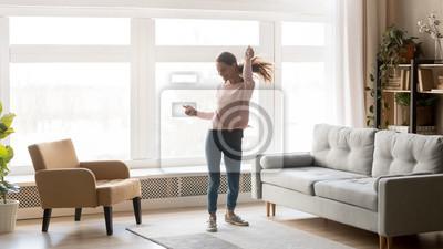 Obraz Happy carefree young woman dancing alone having fun at home