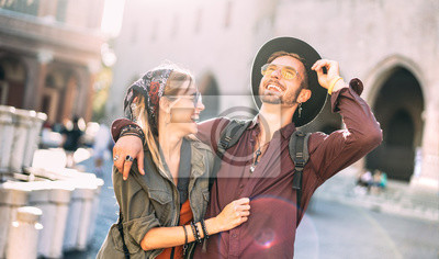 Obraz Happy couple in love having candid fun walking in city center - Wanderlust life style and travel vacation concept with guy and girl at old town tour on warm sunshine filter and backlighting