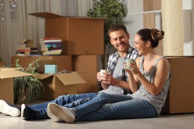 Obraz Happy couple moving home resting and talking