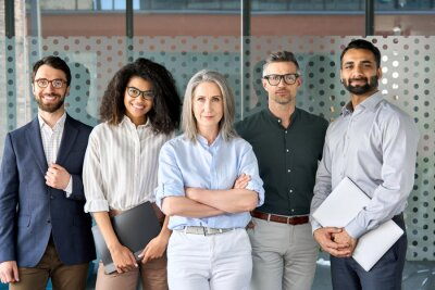 Obraz Happy diverse business people team standing together in office, group portrait. Smiling multiethnic international young professional employees company staff with older executive leader look at camera.
