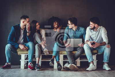 Obraz Happy diverse friends group sharing social media app news sitting holding phones, smiling multiracial young people students showing funny videos on laptop