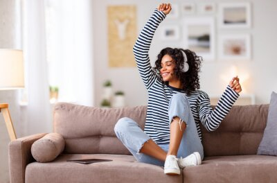 Obraz Happy ethnic woman listening to music and dancing on sofa