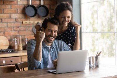 Obraz Happy excited young couple making winner yes hand fist gesture at laptop, getting awesome news, celebrating achieve, success, winning prize, getting unexpected income. Good surprise concept