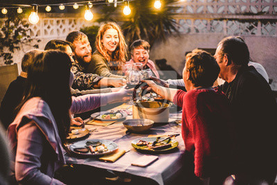 Obraz Happy family cheering with red wine at barbecue dinner outdoor - Different age of people having fun at weekend meal - Food, taste and summer concept - Focus on hands toasting