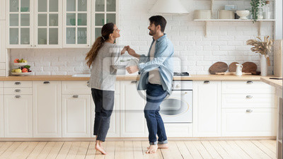 Obraz Happy family couple dancing barefoot on wooden floor in kitchen.