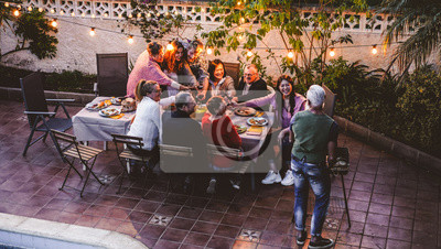 Obraz Happy family eating and cheering with red wine at barbecue party dinner - Different age of people having fun at bbq meal sitting in villa backyard - Summer lifestyle and food concept - Focus on faces