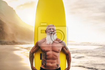 Obraz Happy fit senior having fun surfing at sunset time - Sporty bearded man training with surfboard on the beach - Elderly healthy people lifestyle and extreme sport concept