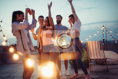 Obraz Happy friends with drinks toasting at rooftop party at night