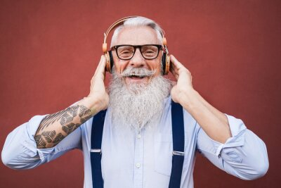 Obraz Happy hipster senior man listening to playlist music outdoors - Focus on face