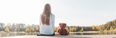 Obraz Happy little girl with stuffed toy teddy bear sitting on wooden pier near calm lake on sunny day back view. Banner web site size