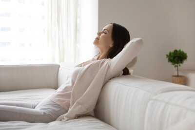 Obraz Happy millennial woman relaxing on sofa, breathing cool air from conditioner, enjoying comfortable climate in ventilated living room, meditating with closed eyes. Comfort at home, conditioning concept