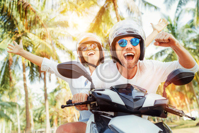 Obraz Happy smiling couple travelers riding motorbike scooter in safety helmets during tropical vacation under palm trees