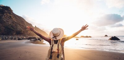 Obraz Happy woman with arms up enjoy freedom at the beach at sunset. Wellness, success, freedom and travel concept