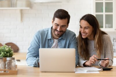 Obraz Happy young couple planning budget, reading good news in email, refund or mortgage approval, smiling woman and man looking at laptop screen, checking finances, sitting at table at home together