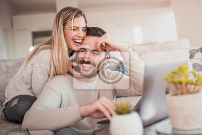 Obraz Happy young couple with laptop at home
