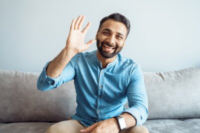 Obraz Headshot portrait of handsome indian man with friendly smile waving to camera