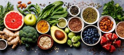 Obraz Healthy food clean eating selection: fruit, vegetable, seeds, superfood, cereal, leaf vegetable on gray concrete background